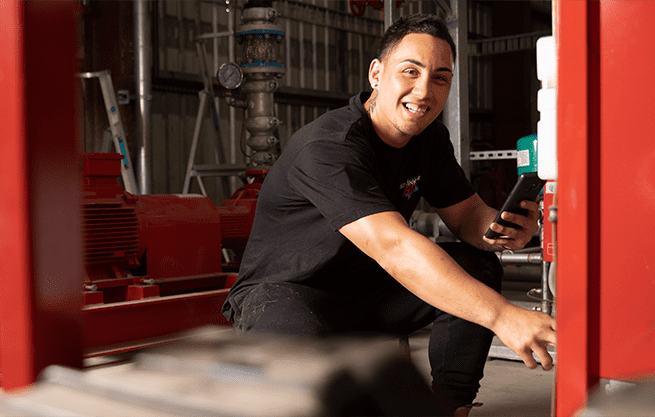 Fire technician maintaining a fire pump with FireMate mobile app